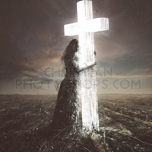 Woman made of dirt clings to the cross