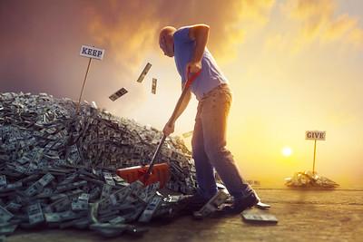 A man shoveling large pile of money.