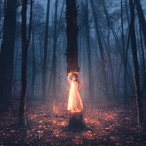 A little girl lifts a tree