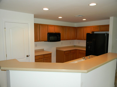 Brand New Black GE Appliances, Corian Countertops, And Real Wood Grain Cabinets!