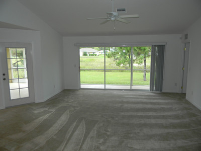 Brand New Carpet In The Living Room With Glass French Door And Triple Sliders The Lead Out To A Screened Lanai!