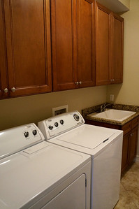 """Laundry room with 36"""" Maple wood cabinets, new appliances and a deep porcelain sink."""