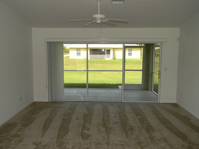 The Living Room Has Brand New Carpeting And Triple Sliders Leading Out To Screened Lanai!
