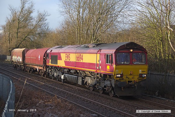 190130-002  DB Cargo class 66/0 No. 66194 is captured passing through Mansfield, powering 6Z20, 09:00 Toton North Yard - Shirebrook, WH Davis. In tow is a covered steel carrier, for use as a barrier vehicle, and a HTA bogie hopper for 'cut & shut mods.