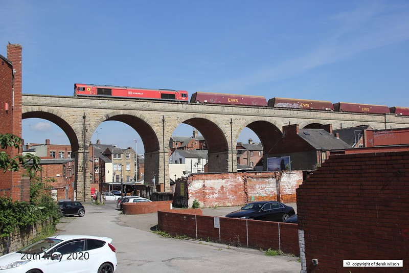 200520-003  DB Cargo class 66/0 No. 66097 is captured crossing Mansfield's 15 arch viaduct, powering train 6V70, 09:58 Worksop up Reception - Cardiff Tidal T.C. In tow are a rake of redundant HTA coal hoppers for cutting up. Coal trains were common place as Mansfield was in the heart of the Nottinghamshire coal fields, but sadly, this could well be the last time that a full rake of coal hoppers will traverse the viaduct, although some have, and still are being converted for use in the aggregates sector.