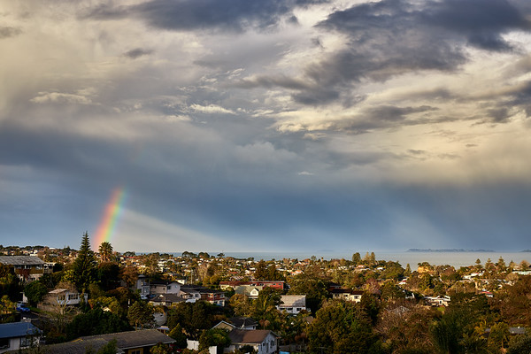 Rainbow season over Torbay on Auckland's North Shore as a weather system passes over the Hauraki Gulf