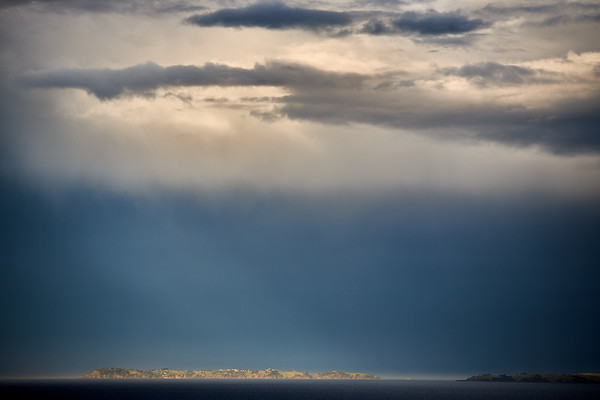 The island of Motutapu in Auckland's Hauraki Gulf catches a burst of sunshine on a stormy day