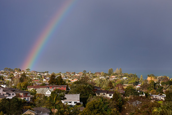 Rainbow season over Torbay on Auckland's North Shore as a weather system passesover the Hauraki Gulf