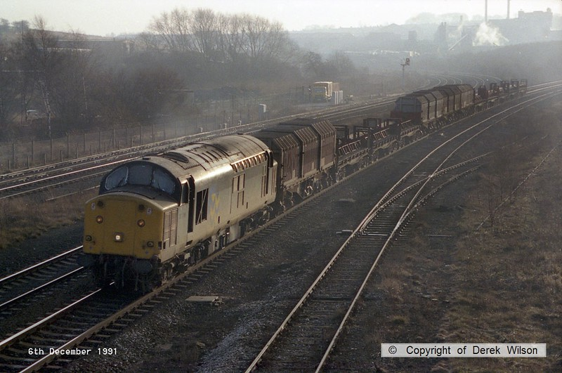 911206-003     Trainload Metals class 37/7 no 37716 passes through Clay Cross with a northbound freight, made up of steel coil wagons. Before being refurbished into the 37/7 sub class this was no 37094.