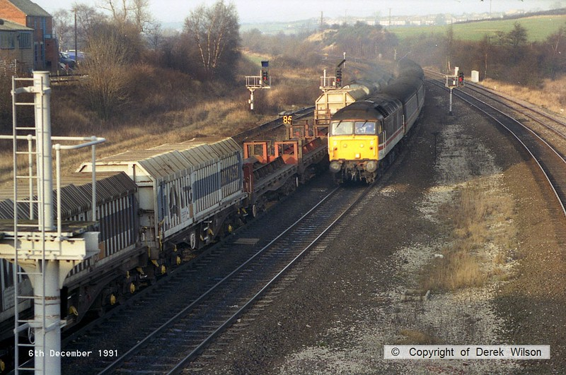 911206-004     Trainload Metals class 37/7 no 37716 waits to cross over to the freight lines at Clay Cross, with a rake of steel coil carriers. Heading towards the camera with a southbound Intercity cross country service is, class 47/8 no 47814.