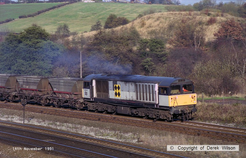 911114-008     Trainload Coal class 58 no 58030 passes Clay Cross, heading south on the Erawash line, powering a rake of empty coal hoppers.