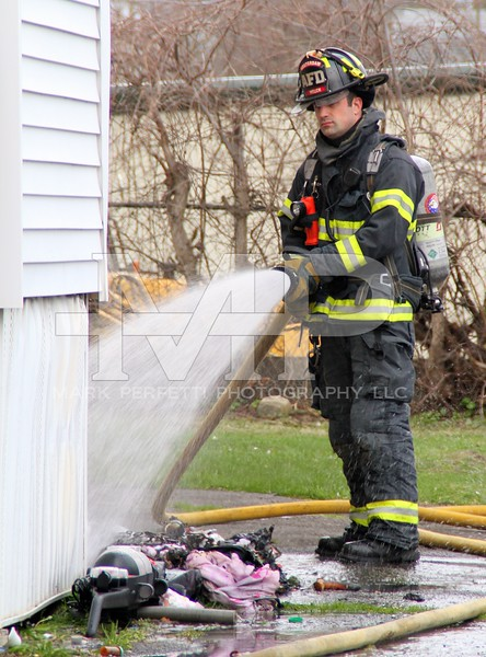Amsterdam Firefighter Mike Welch douses the pile of debris and clothing outside the residence