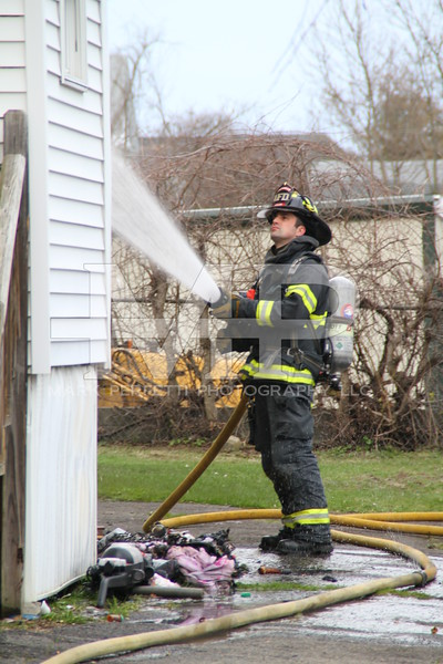 Amsterdam Firefighter Mike Welch douses the outside of the structure