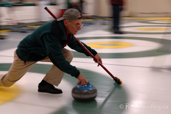 Curling action at the Granite Curling Club of West Ottawa. This session took place in a low light situation. High level of digital noise in these photographs make them ideally suited for web use or small prints. Therefore only low resolution downloads and small prints have been activated in the buy options. This image is model released. © Rob Huntley