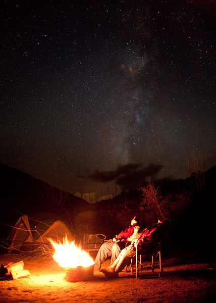 This is Louise and I sitting out by the campfire looking up at the stars.  What you see in the background is the Milky Way. Some clouds are at the  bottom of the picture.