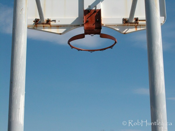 Basketball hoop from behind with blue sky and clouds in background.