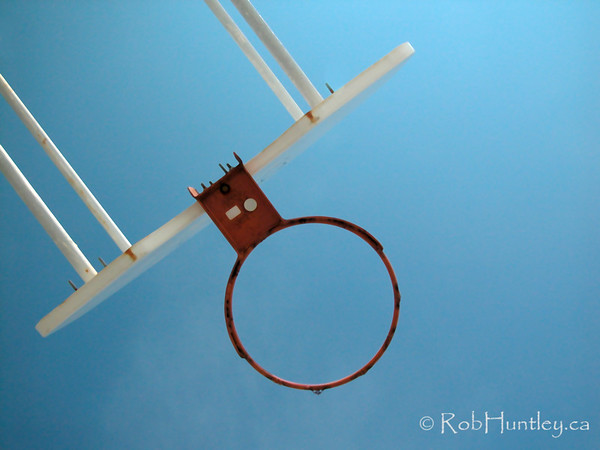 Basketball hoop from below with blue sky background.