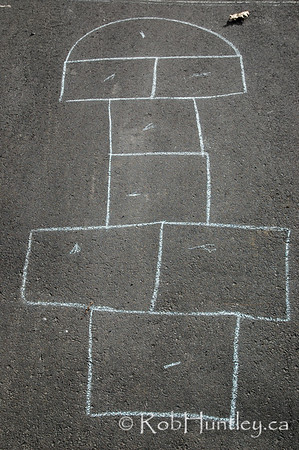 Hopscotch game outline drawn in chalk on driveway.