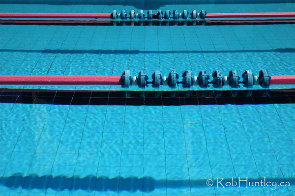 Swimming pool lane marker ropes and black lines on the bottom.