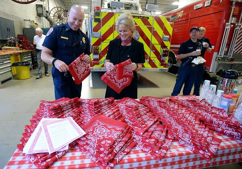"Loveland Fire Rescue Authority battalion chief Tim Smith, left, gets a red bandana from Lisa Melby, center, with Good Samaritan Society Loveland Village, before grabbing some breakfast Monday, Sept. 11, 2017, at fire station 1 in downtown Loveland. Good Samaritan gave out red bandanas and breakfast to first responders in Loveland to thank and honor them and the ""man in the red bandana,"" who helped carry people to safety from the World Trade Center in 2001 and perished in the attack. (Photo by Jenny Sparks/Loveland Reporter-Herald)"