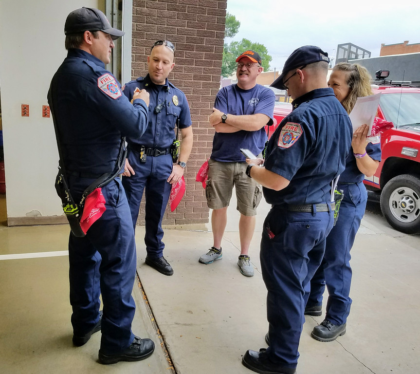 . From left, Loveland Fire Rescue Authority firefighter Braden Marker, Battalion Chief Tim Smith, Battalion Chief Jason Starck, Engineer Gina Gonzalez and Battalion Chief Michael Cerovski chat at a breakfast event Monday morning at the downtown fire station with red bandanas they received for First Responders Red Bandana Day. (Sam Lounsberry / Loveland Reporter-Herald)