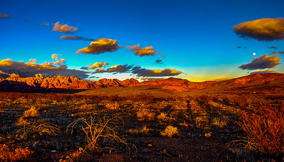 The Moon over the Candy Cliffs illuminated by the setting sun in the Red Cliffs Deseret National Conservation Area, Utah, USA