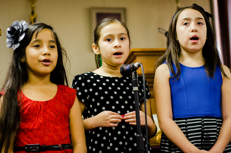 Giselle Cintron, 7, Isabella Ayapan, 8, and Nicole Delgado, 8, entertain the crowd with Christmas carols during the Red Kettle Kickoff at the Salvation Army in Fitchburg on Saturday morning. SENTINEL & ENTERPRISE / Ashley Green