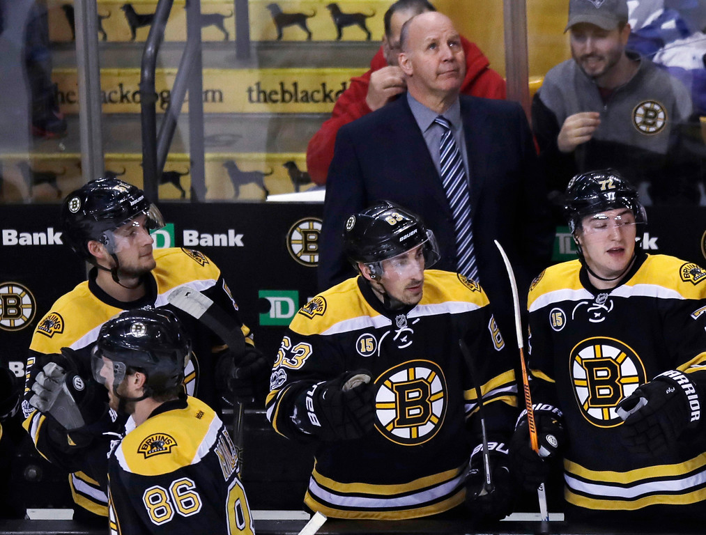 . Boston Bruins head coach Claude Julien looks up at the scoreboard as Boston Bruins defenseman Kevan Miller (86) is congratulated after a goal during the first period of an NHL hockey game against the Detroit Red Wings in Boston, Tuesday, Jan. 24, 2017. (AP Photo/Charles Krupa)