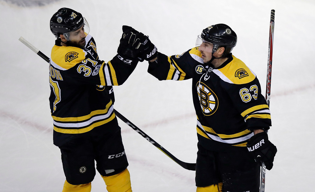 . Boston Bruins left wing Brad Marchand (63) is congratulated by Patrice Bergeron after his goal against Detroit Red Wings goalie Jared Coreau during the first period of an NHL hockey game in Boston, Tuesday, Jan. 24, 2017. (AP Photo/Charles Krupa)