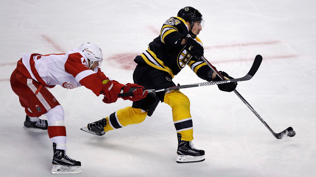 . Boston Bruins left wing Brad Marchand, right, shoots as Detroit Red Wings right wing Gustav Nyquist, left, tries to block during the first period of an NHL hockey game in Boston, Tuesday, Jan. 24, 2017. (AP Photo/Charles Krupa)