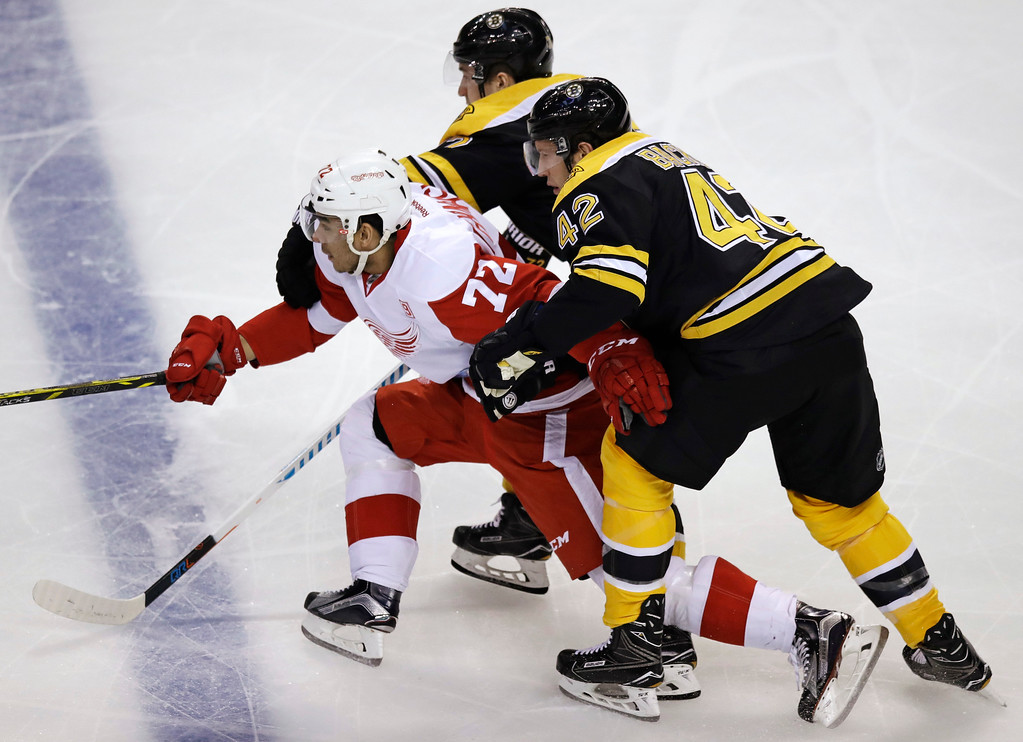 . Detroit Red Wings center Andreas Athanasiou (72) is held back as he threads between Boston Bruins right wing David Backes (42) and center Frank Vatrano, rear, during the first period of an NHL hockey game in Boston, Tuesday, Jan. 24, 2017. (AP Photo/Charles Krupa)