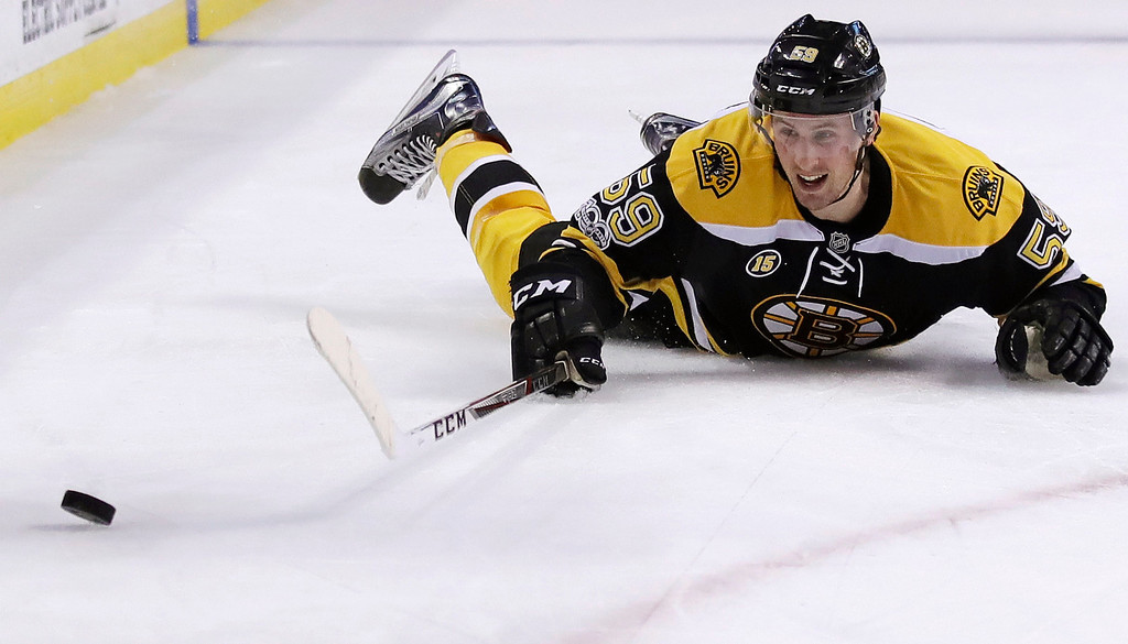 . Boston Bruins center Tim Schaller (59) slides after the puck against the Detroit Red Wings during the second period of an NHL hockey game in Boston, Tuesday, Jan. 24, 2017. (AP Photo/Charles Krupa)