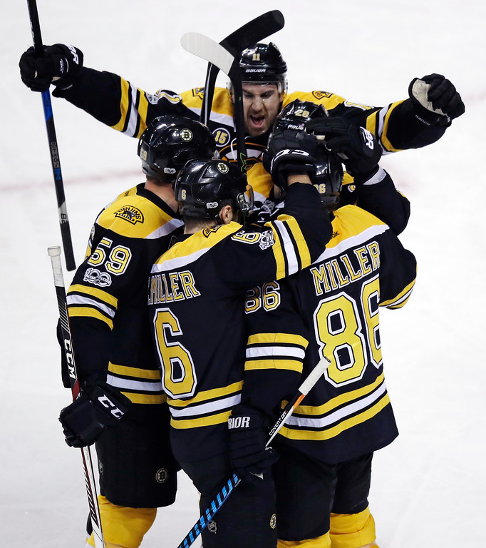 . Boston Bruins defenseman Kevan Miller (86) is congratulated by teammates after his goal against Detroit Red Wings goalie Jared Coreau during the first period of an NHL hockey game in Boston, Tuesday, Jan. 24, 2017. At rear raising arms is Boston Bruins right wing Jimmy Hayes. (AP Photo/Charles Krupa)
