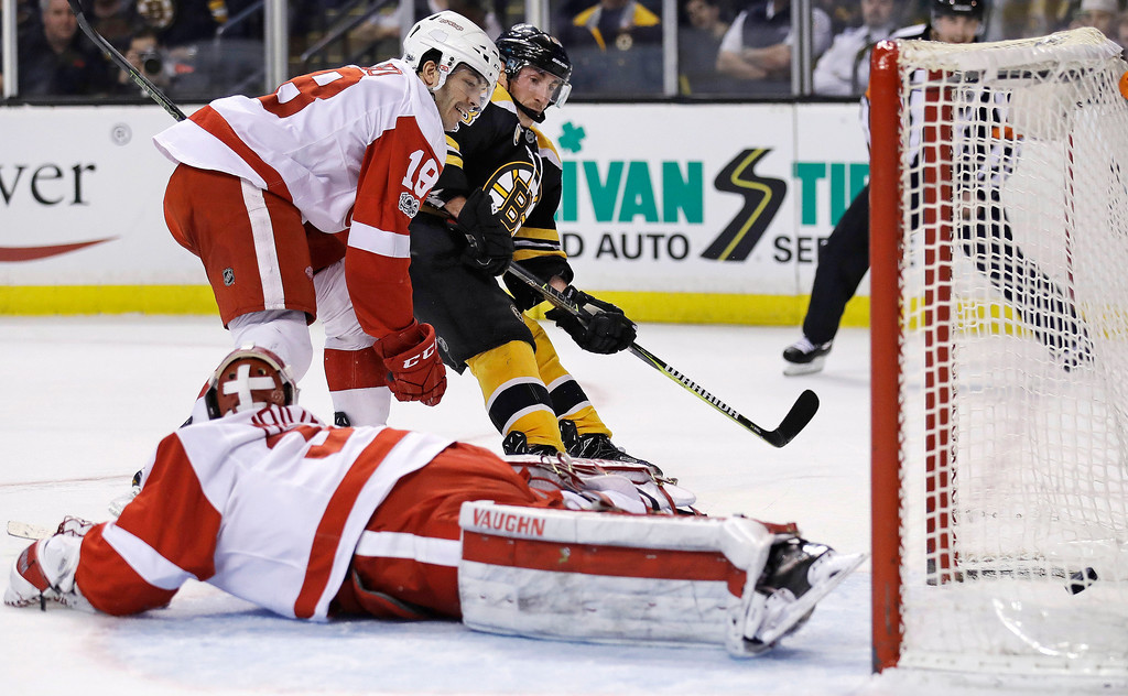 . Boston Bruins left wing Brad Marchand, center, finds an opening for a goal behind Detroit Red Wings goalie Petr Mrazek (34) during the second period of an NHL hockey game in Boston, Wednesday, March 8, 2017. At left is defenseman Robbie Russo (18). (AP Photo/Charles Krupa)