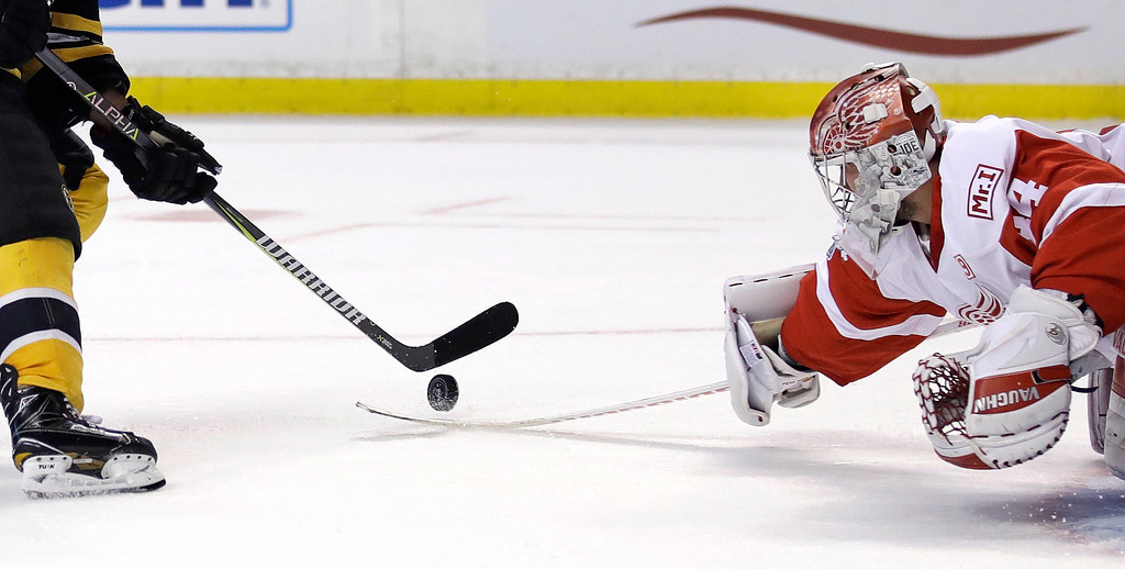 . Detroit Red Wings goalie Petr Mrazek, right, tries unsuccessfully to knock the puck off the stick of Boston Bruins left wing Brad Marchand on a goal during the second period of an NHL hockey game in Boston, Wednesday, March 8, 2017. (AP Photo/Charles Krupa)