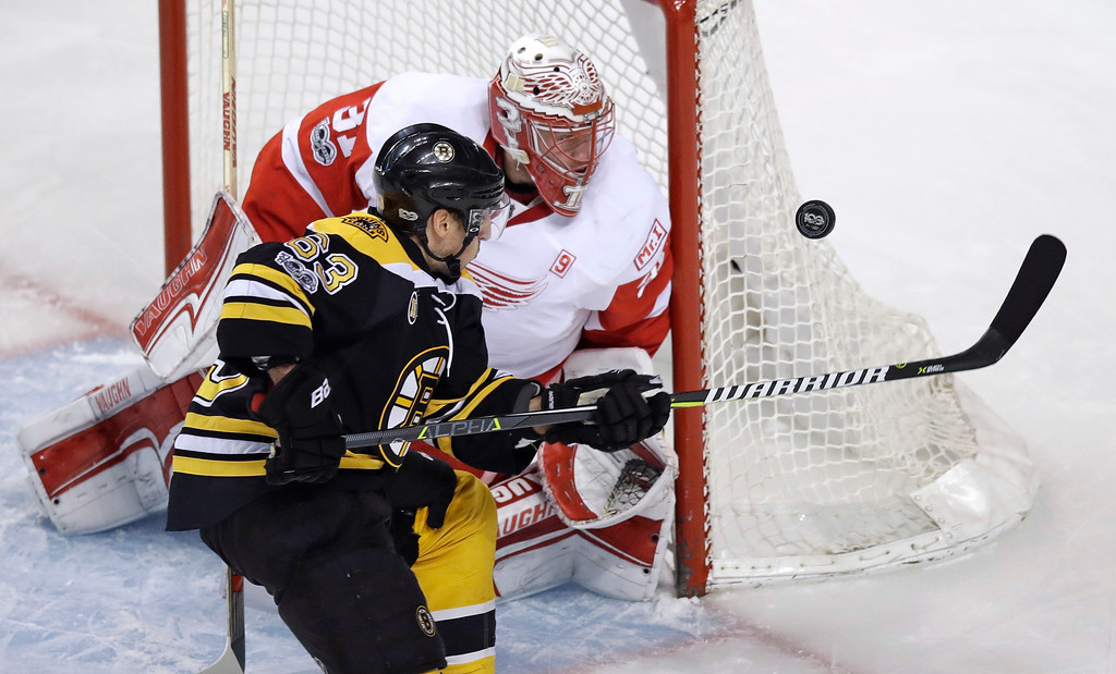 . Boston Bruins left wing Brad Marchand (63) tries to tip the puck down against Detroit Red Wings goalie Jared Coreau (31) during the first period of an NHL hockey game in Boston, Wednesday, March 8, 2017. (AP Photo/Charles Krupa)
