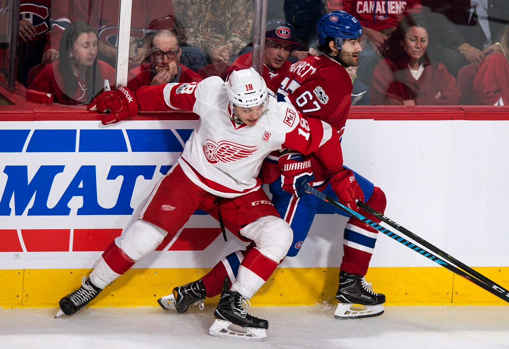 . Detroit Red Wings\' Robbie Russo (18) hangs on to Montreal Canadiens\' Max Pacioretty (67) during the second period of an NHL hockey game in Montreal on Tuesday, March 21, 2017. (Paul Chiasson/The Canadian Press via AP)