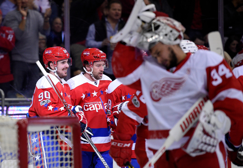 . Washington Capitals left wing Marcus Johansson (90), of Sweden, celebrates his goal with Justin Williams, second from left, as Detroit Red Wings goalie Petr Mrazek (34), of the Czech Republic, looks on during the first period of an NHL hockey game, Thursday, Feb. 9, 2017, in Washington. (AP Photo/Nick Wass)