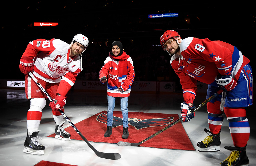 . Fatima Al Ali, of the United Arab Emirates, center, takes part in a ceremonial puck drop before an NHL hockey game with Washington Capitals left wing Alex Ovechkin (8), of Russia, and Detroit Red Wings left wing Henrik Zetterberg (40), of Sweden, Thursday, Feb. 9, 2017, in Washington. (AP Photo/Nick Wass)