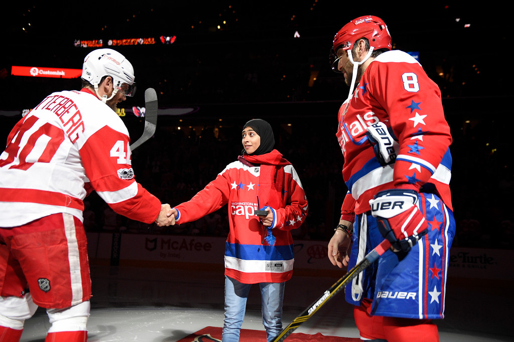 . Fatima Al Ali, of the United Arab Emirates, center, shakes hands with Detroit Red Wings left wing Henrik Zetterberg (40), of Sweden, after a ceremonial puck drop before an NHL hockey game as Washington Capitals left wing Alex Ovechkin (8), of Russia, looks on, Thursday, Feb. 9, 2017, in Washington. (AP Photo/Nick Wass)