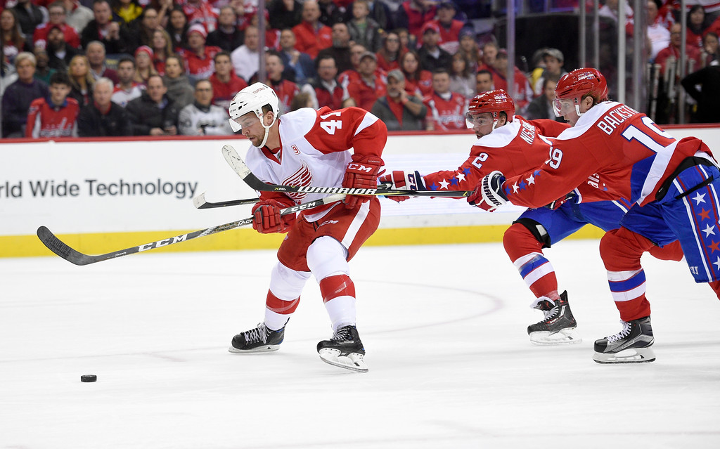 . Detroit Red Wings center Luke Glendening (41) skates with the puck past Washington Capitals defenseman Matt Niskanen (2) and center Nicklas Backstrom (19), of Sweden, during the second period of an NHL hockey game, Thursday, Feb. 9, 2017, in Washington. (AP Photo/Nick Wass)
