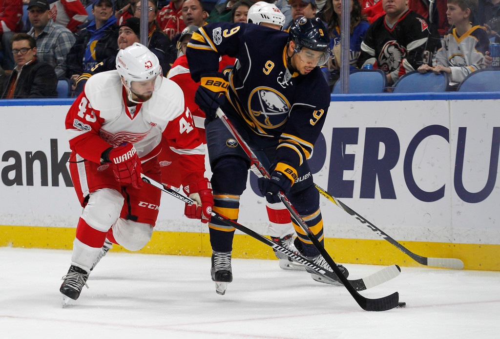 . Buffalo Sabres forward Evander Kane (9) is pressured by Detroit Red Wings forward Darren Helm (43) during the first period of an NHL hockey game, Friday, Jan. 20, 2017, in Buffalo, N.Y. (AP Photo/Jeffrey T. Barnes)