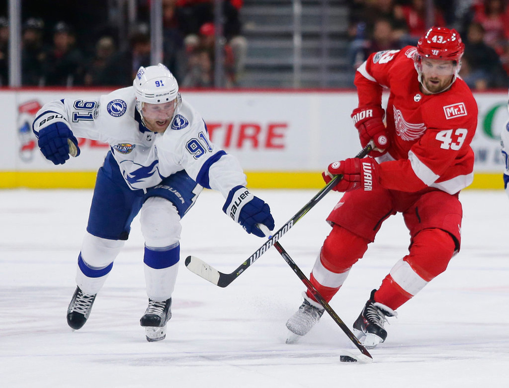 . Tampa Bay Lightning center Steven Stamkos (91) tries to steal the puck from Detroit Red Wings left wing Darren Helm (43) during the second period of an NHL hockey game Monday, Oct. 16, 2017, in Detroit. The Lightning defeated the Red Wings 3-2. (AP Photo/Duane Burleson)