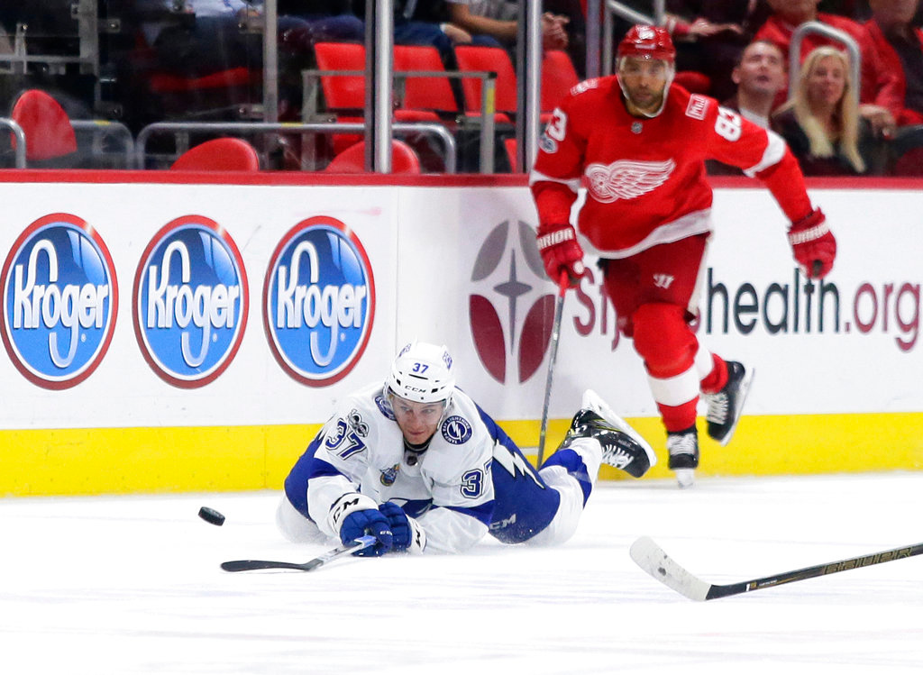 . Tampa Bay Lightning center Yanni Gourde (37) sends the puck toward the Detroit Red Wings goal as he is pursued by Detroit Red Wings defenseman Trevor Daley (83) during the third period of an NHL hockey game Monday, Oct. 16, 2017, in Detroit. (AP Photo/Duane Burleson)