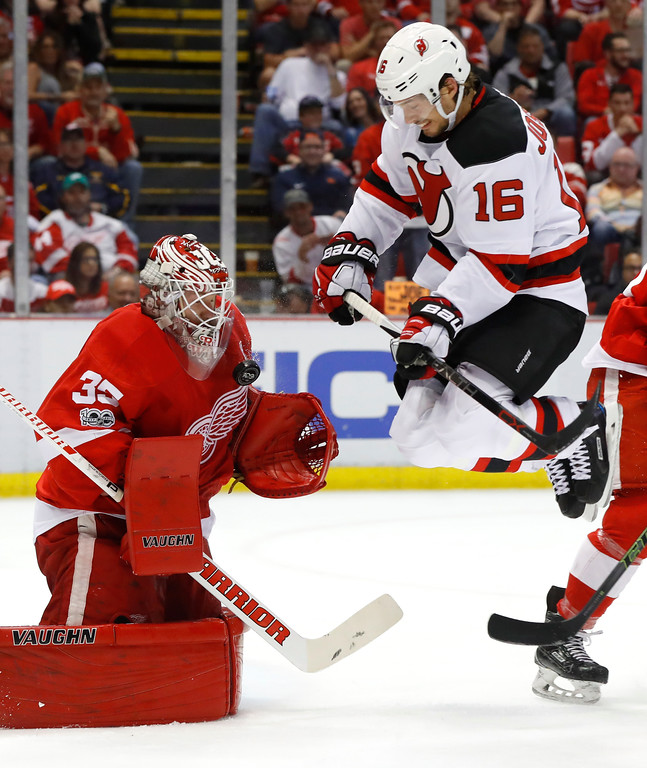 . New Jersey Devils center Jacob Josefson (16) jumps as Detroit Red Wings goalie Jimmy Howard (35) stops a shot during the first period of the final NHL hockey game at Joe Louis Arena, Sunday, April 9, 2017, in Detroit. (AP Photo/Paul Sancya)