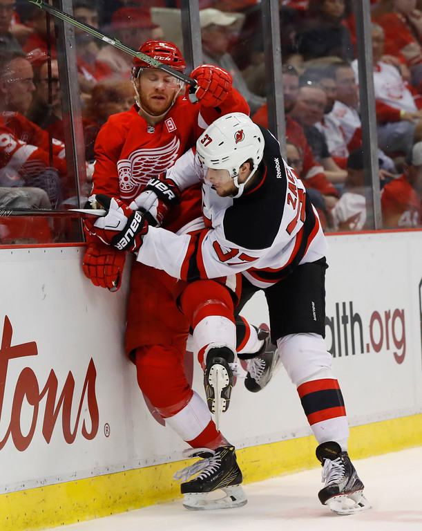 . New Jersey Devils center Pavel Zacha (37) checks Detroit Red Wings defenseman Nick Jensen (3) during the first period of the final NHL hockey game at Joe Louis Arena, Sunday, April 9, 2017, in Detroit. (AP Photo/Paul Sancya)