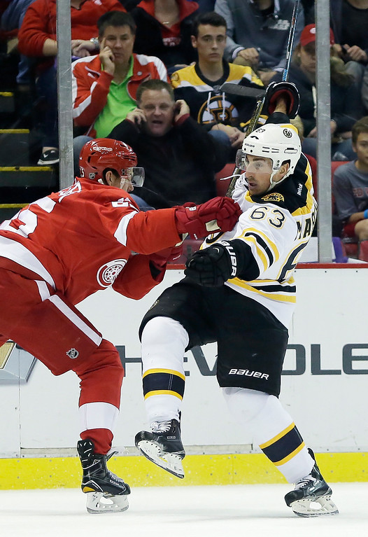 . Detroit Red Wings defenseman Danny DeKeyser, left, knocks Boston Bruins left wing Brad Marchand (63) off his skates during the first period of an NHL hockey game Saturday, Oct. 29, 2016, in Detroit. (AP Photo/Duane Burleson)