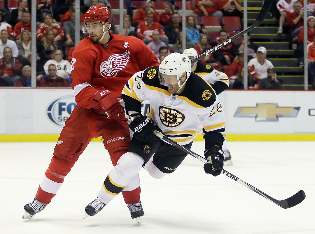 . Boston Bruins center Dominic Moore (28) is knocked off his skates by Detroit Red Wings defenseman Brendan Smith (2) after shooting on goal during the third period of an NHL hockey game Saturday, Oct. 29, 2016, in Detroit. (AP Photo/Duane Burleson)