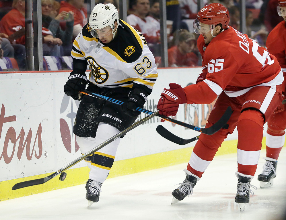 . Detroit Red Wings defenseman Danny DeKeyser (65) tries to steal the puck from Boston Bruins left wing Brad Marchand (63) during the first period of an NHL hockey game Saturday, Oct. 29, 2016, in Detroit. (AP Photo/Duane Burleson)