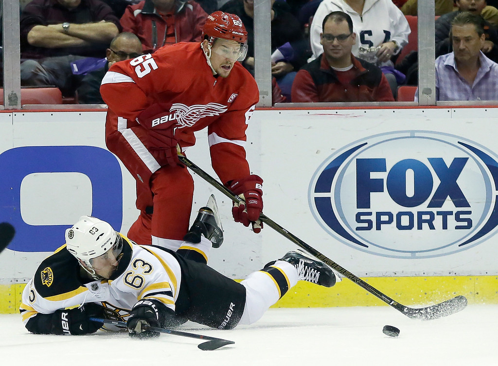 . Detroit Red Wings defenseman Danny DeKeyser (65) steals the puck from Boston Bruins left wing Brad Marchand (63) during the first period of an NHL hockey game Saturday, Oct. 29, 2016, in Detroit. (AP Photo/Duane Burleson)